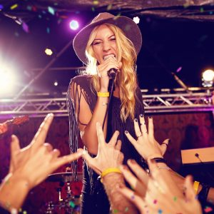 Female-singer-on-stage-with-hat-and-enthusiastic-audience