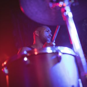 male-drummer-performing-at-music-concert