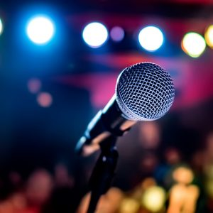 microphone-on-stage-against-a-background-of-audito-PZ3UK59-scaled-1